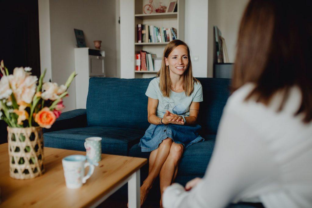 Stephanie sitzt auf der Couch und hat eine Klientin zu einer Beratung zu Besuch